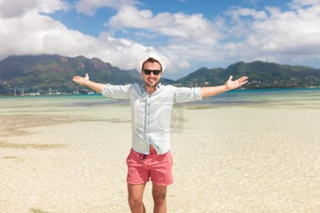 Photo for Young casual man celebrating freedom on the beach with hands outstretched - Royalty Free Image