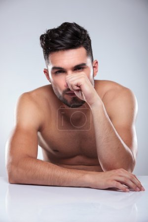 Seated naked man with hand covering his face