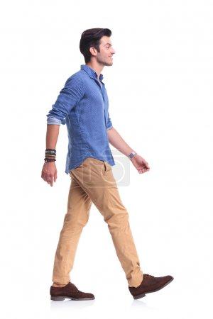 Photo pour Vue latérale d'un souriant jeune homme décontracté à pied, sur fond blanc - image libre de droit