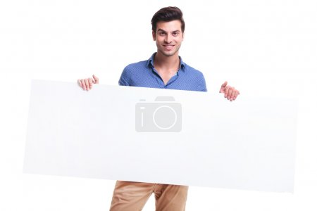 smiling casual man holding big blank board