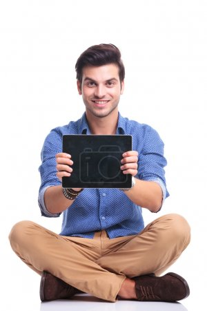Photo for Young smiling seated man showing the screen of his tablet pad computer on white background - Royalty Free Image