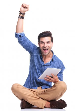 man celebrating success while working on tablet