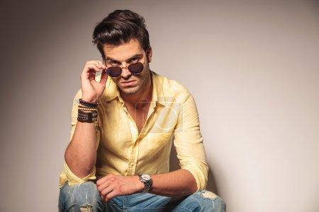 Photo pour Homme de mode enlever ses lunettes de soleil et regarde vers la caméra alors qu'il est assis sur la chaise - image libre de droit