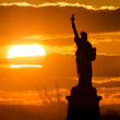 Photo of the Statue of liberty in sunset fire made...