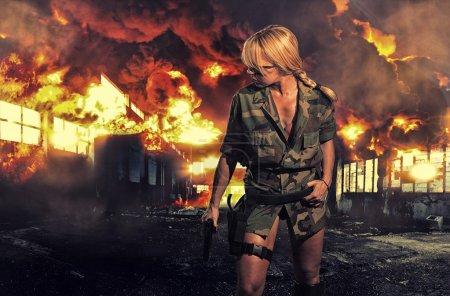 Photo pour Tactique spéciale femme sexy tenant son arme avec explosion derrière elle - image libre de droit