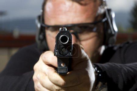 Photo pour Homme tirant sur un champ de tir extérieur, mise au point sélective - image libre de droit