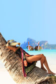 Woman sitting on a coconut tree on Phi Phi