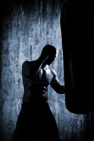 Photo pour Homme Boxer pendant sac lourd de boxe hiting à l'entraînement de fitness - image libre de droit