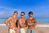 Three handsome men at the beach