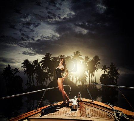 Photo pour Jeune femme sexy sur son yacht privé au coucher du soleil autour de l'île tropicale - image libre de droit