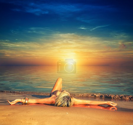 Photo for Beautiful young woman in bikini on the beach at sunset - Royalty Free Image