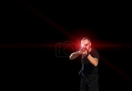 Man aiming assault rifle laser
