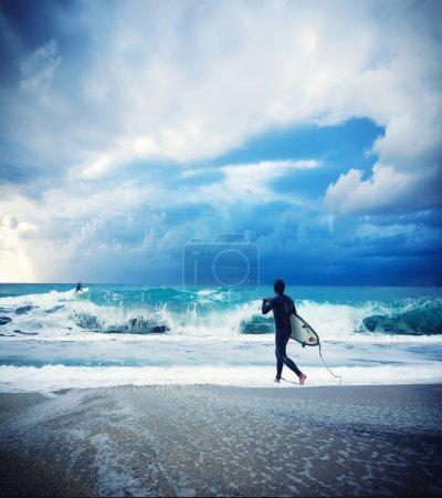 Foto de Joven surfista masculino de pie en la playa con tabla de surf mirando al océano . - Imagen libre de derechos