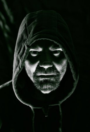 Scary evil man with hood in darkness...