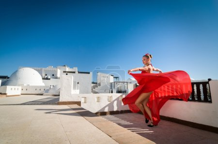 Photo for Attractive flamenco dancer wearing traditional red dress with flower in her hair - Royalty Free Image