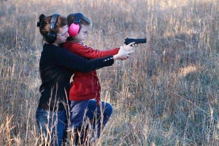 Photo pour Mère enseignant à sa jeune fille comment utiliser correctement et en toute sécurité une arme de poing . - image libre de droit