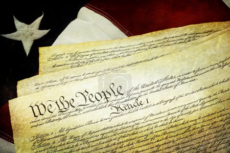 Textured American Constitution lying over top of t...