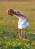 Roztomilé děvčátko v bílých šatech, zkoumání louku na slunný jarní den