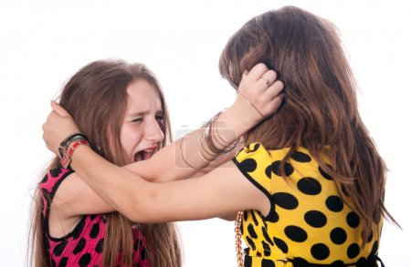 Two teenage girls pulling each others hair out isolated on white