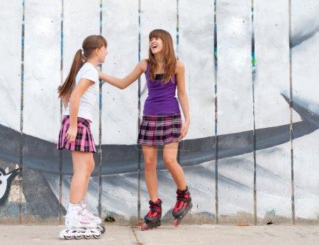 Two cute teenage girls on roller skates having fun in urban environment