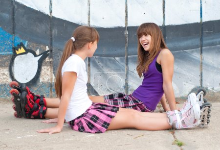 Two happy teenage girls in roller skates and short skirts having fun in urban environment