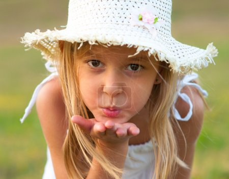 Photo for Cute little girl on the meadow blowing a kiss toward you on beautiful summer day - Royalty Free Image