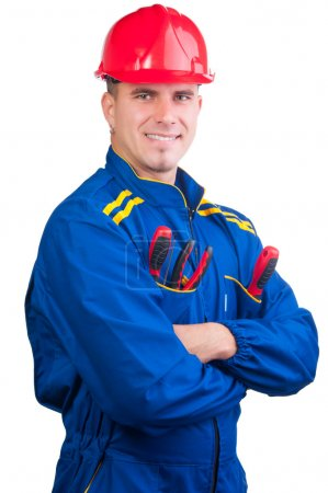 Young handsome mechanic with hard hat and tools and in overalls isolated on white
