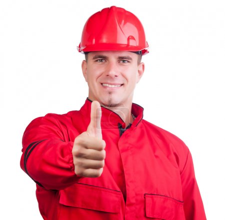Young smiling fireman with hard hat and in full uniform showing thumbs up isolated on white.