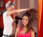 Hairdresser making hair of beautiful teenage girl