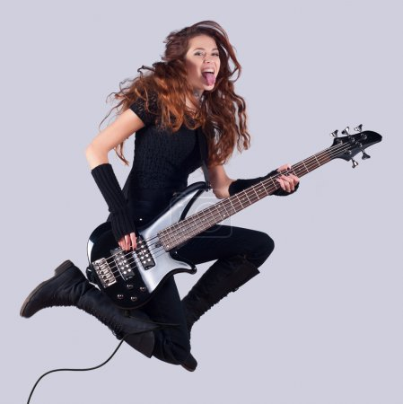 Beautiful smiling girl with bass guitar jumping high in the air