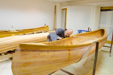 Young carpenter examining new canoe