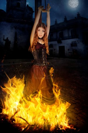 Photo pour Belle jeune sorcière dans les flammes du feu - image libre de droit