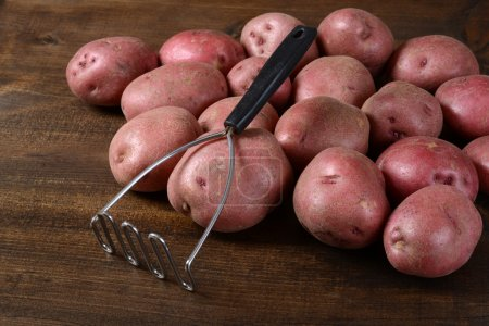 Old potato masher with red potatoes on wood...