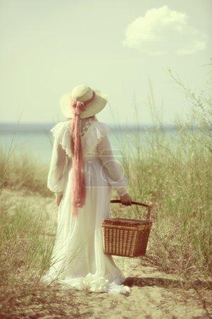 Photo pour Portrait de femme vintage à la plage avec panier pique-nique - image libre de droit