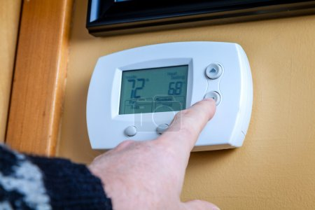 A person lowers temperature on a home thermostat. ...