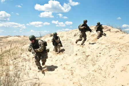 Photo pour Escouade de soldats traversent le désert à travers l'opération militaire - image libre de droit