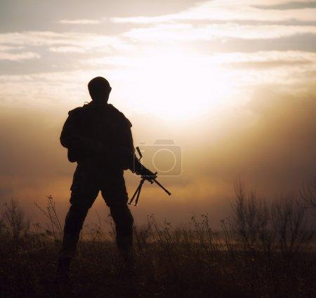 Photo pour Silhouette nous marine avec fusil contre le coucher de soleil - image libre de droit