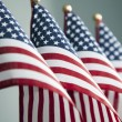 Four American flags stand in a row....