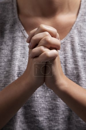 Photo for A yound woman clasps her hands in prayer. - Royalty Free Image