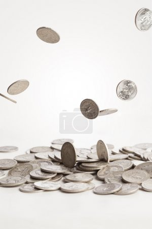 A group of silver coins are falling down into a pi...