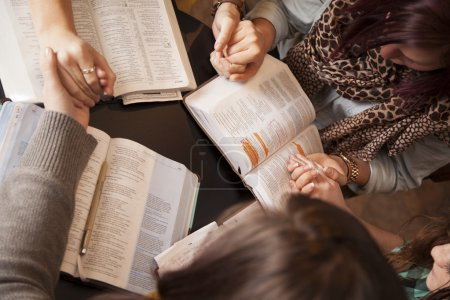 Photo for A group of young women bow their heads and pray with bibles. - Royalty Free Image