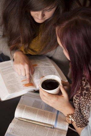 Photo pour Deux jeunes femmes étudient la Bible ensemble en buvant du café . - image libre de droit