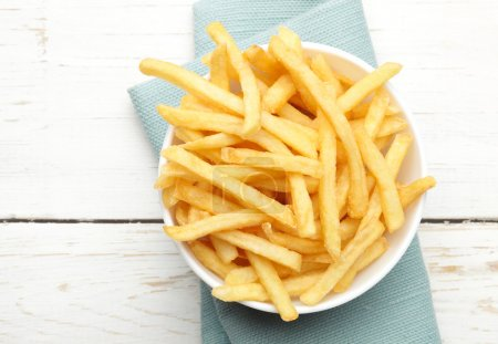 Photo for Bowl of french fries on white wooden surface - Royalty Free Image