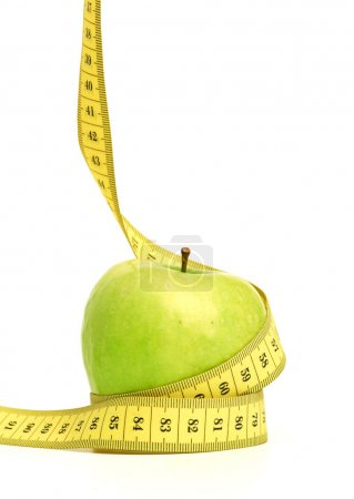 Photo for Green apple with yellow measuring tape against white background - Royalty Free Image