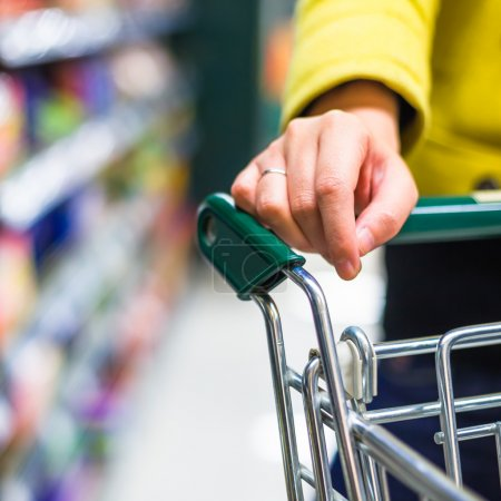 Closeup of female shopper with trolley at supermarket