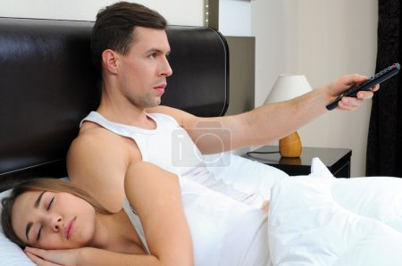 Man watches television and his wife sleeps