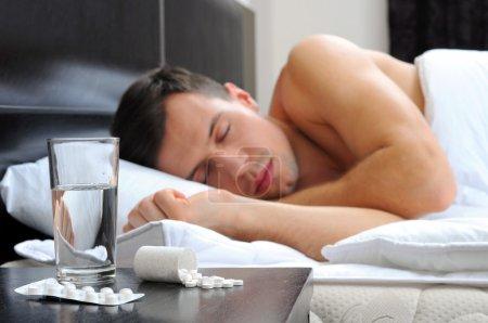 Man sleeping - pills on bed table