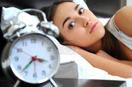 Clock with sleep at night. Woman can not sleep