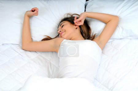 Young beautiful, woman waking up fully rested