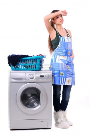 Young house wife near washing machine with loundry